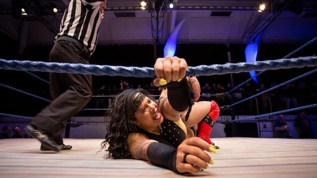 Une lutteuse crie au sol en tenant une des cordes du ring.