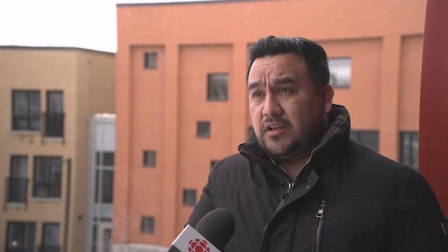 Luis-Carlos Cuasquer parle dans un micro devant un immeuble.