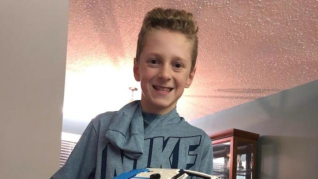 Un garçon sourit à la caméra et tient dans ses mains une voiture jouet.