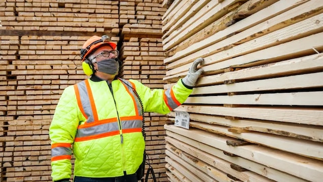 Darcy Elliott, shipping supervisor at Spray Lake Sawmills, inspects lumber at the company's facility in Cochrane, Alta. in May.