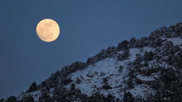 La Lune presque pleine est vue derrière une montagne en Corse.
