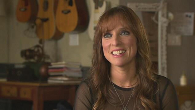 La chanteuse Lynda Lemay, dans sa maison, devant un mur où sont accrochées des guitares.