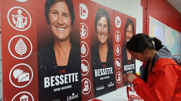 L'attachée assemble des cocardes devant des pancartes électorales de Lyne Bessette.