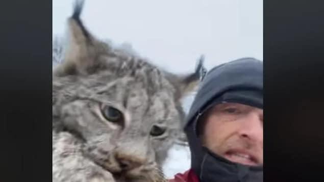 Un homme tient un lynx par la nuque.