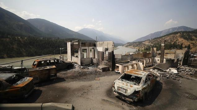 Des voitures brûlées devant les ruines d'un bâtiment.
