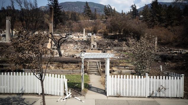 Une clôture blanche avec des décombres à l'arrière.