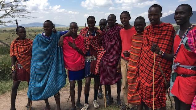 Un groupe d'hommes maasaïs, vêtus de tissus rouges, roses et bleus.