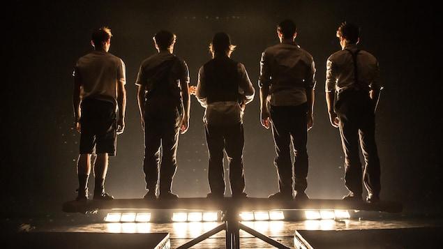 Des membres de la troupe Machine de Cirque, de dos, lors d'un spectacle