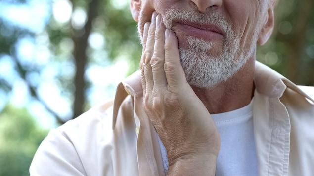 Un homme se tient la mâchoire et semble souffrir.
