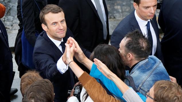 Le président français sert la main de passants à l'Arc de Triomphe.