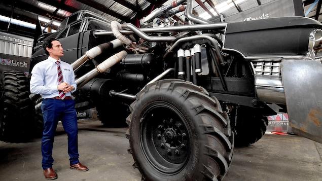Un homme pose devant une voiture du film Mad Max Fury Road.