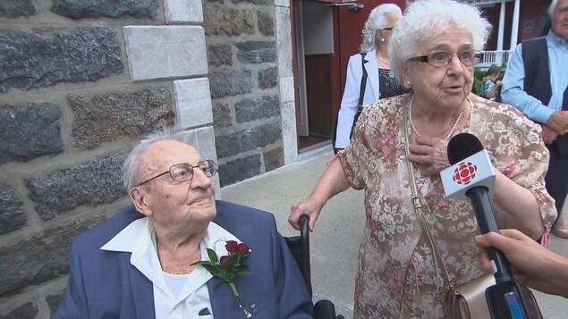 Accompagnée de son conjoint, une femme âgée répond aux questions de la journaliste.