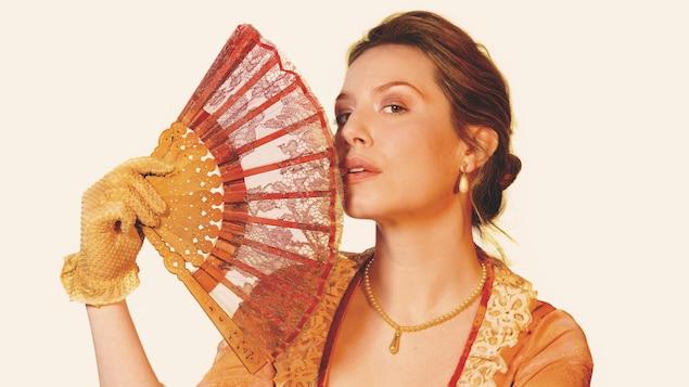 Une femme en robe d'époque tient un éventail près de sa bouche.