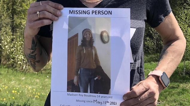 Une personne exhibe une affiche de personne disparue.