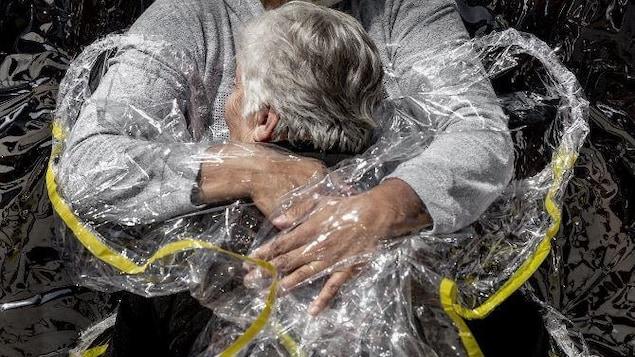 Une femme âgée fait un câlin à une jeune femme portant un masque. Les deux femmes sont séparées par une feuille plastique.