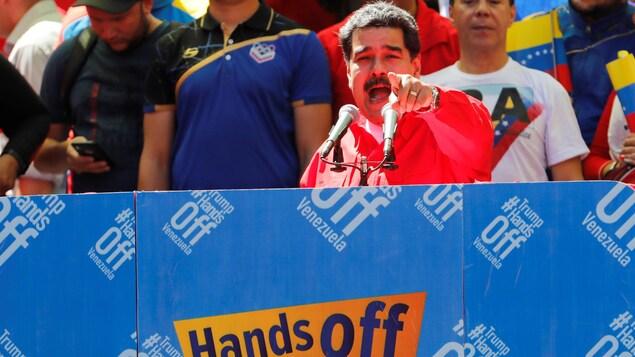 Un homme pointe du doigt dans la direction de la caméra alors qu'il livre un discours derrière deux micros sur une estrade sur laquelle il  est écrit en anglais: «Trump ne touche pas au Venezuela».