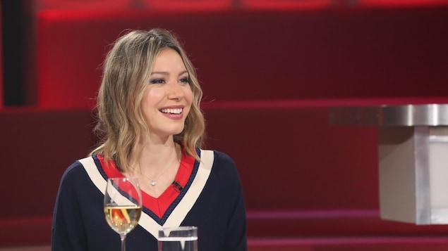 Vêtue d'un chandail marine, la comédienne sourit et regarde sur le côté.