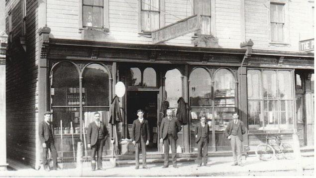 Six hommes se tiennent debout devant un magasin général dans les années 1900.