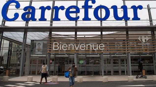 Des clients sortant du supermarché Carrefour.