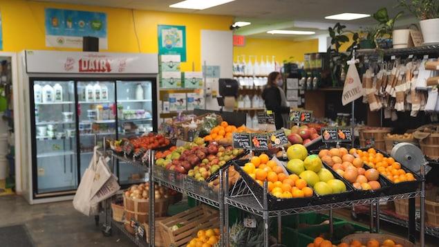 Un rayon de fruits, dont des pommes et des oranges, avec des bouteilles de lait dans un frigidaire dans un magasin d'alimentation.