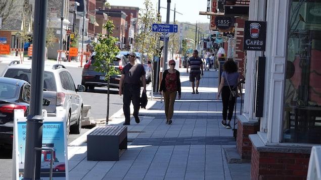 Des gens marchent sur un trottoir en pavé uni