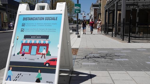 Une pancarte rappelant la distanciation sociale est apposée sur un trottoir d'une rue du centre-ville de Magog