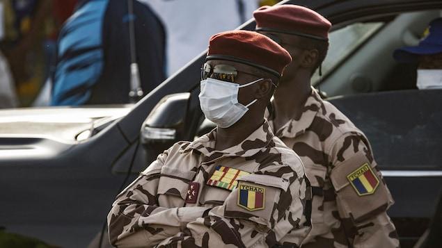L'homme, portant un uniforme de l'armée, se tient debout les bras croisés.