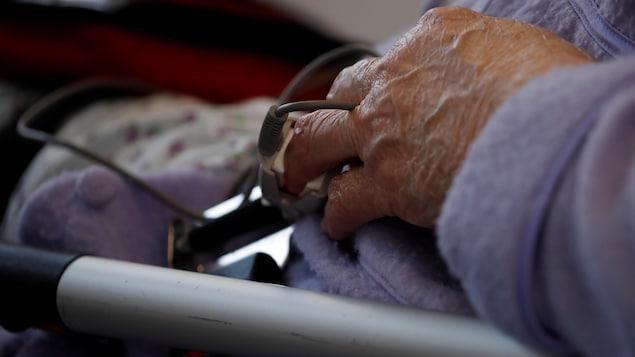 Le doigt de la patiente est enserré dans un dispositif qui mesure les signes vitaux