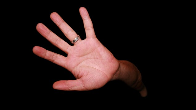 Une main apparaît dans le noir.