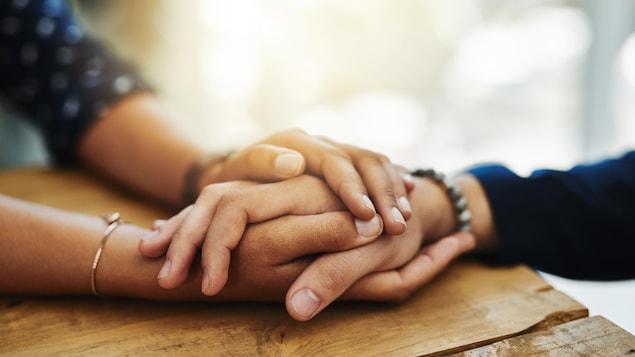Deux mains en enserrent une autre sur une table.