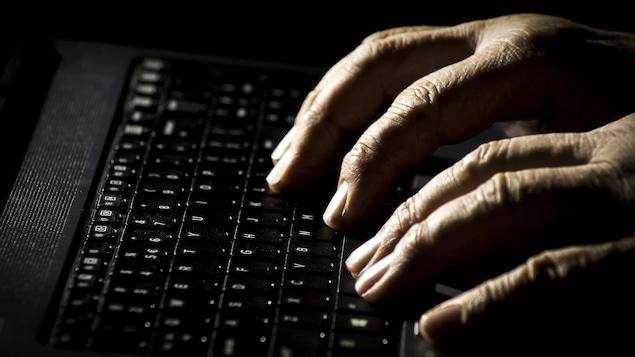 Les mains d'un vieil homme sur un clavier d'ordinateur portable.