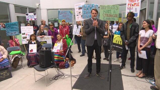 Charlie Clark parle dans un micro, entouré de plusieurs personnes avec des pancartes à la main.