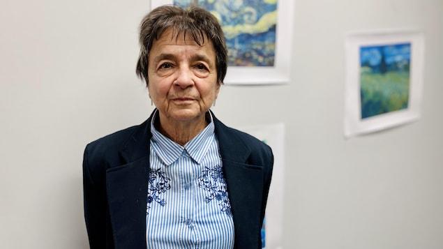 Une femme pose devant un mur blanc avec des toiles.