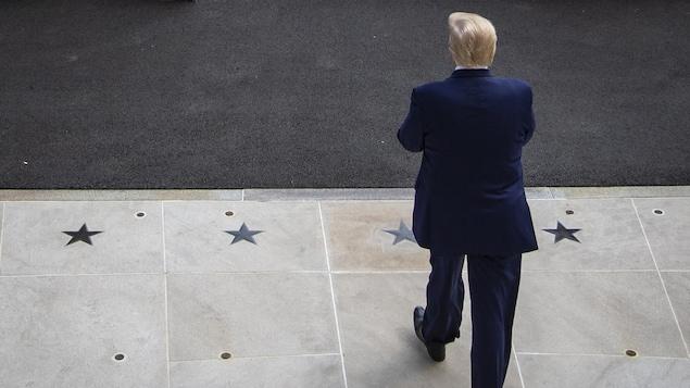 Vu de dos (et de haut), le président Trump sort de la Maison-Blanche.