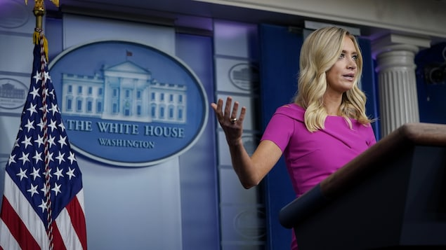 Elle est derrière un lutrin et devant le logo de la Maison-Blanche et le drapeau américain.
