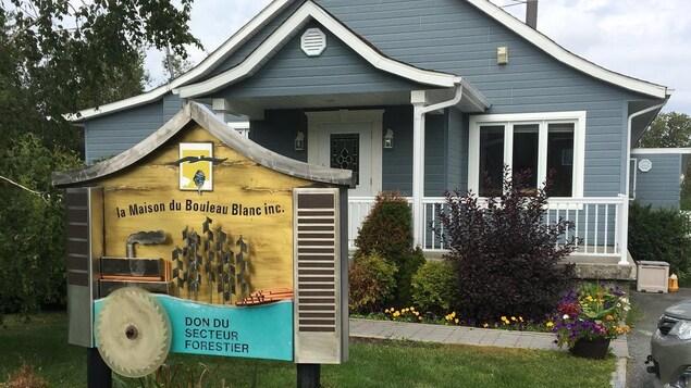 Bâtiment bleu s'apparentant à une résidence, avec une affiche au devant indiquant le nom du centre de soins palliatifs, la « Maison du Bouleau blanc ».