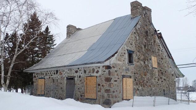 Abandonnée depuis des années, la maison Charbonneau à Laval est dans un piteux état. Sur la photo, toutes les fenêtres et les portes sont placardées.