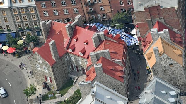 La maison Chevalier, et les rues environnantes avec l'animation des jours été et les parasols aux terrasses, vue des airs