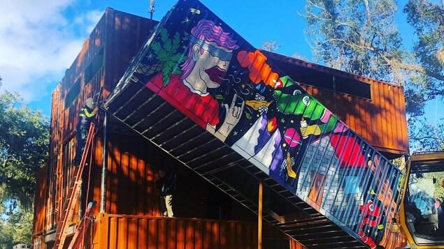 Un conteneur dont un des côtés affiche une murale en train d'être installé sur la maison à l'aide d'une grue.