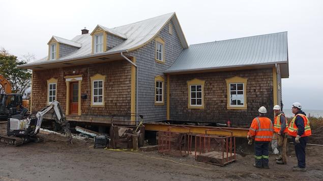 Des travailleurs de la construction observent une maison ancestrale qui doit être déplacée du bord du fleuve Saint-Laurent, à Rimouski.