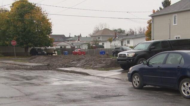 Le terrain vide entre deux résidences est rempli par un tas de terre