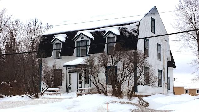 Une maison du 19e siècle entourée de neige.