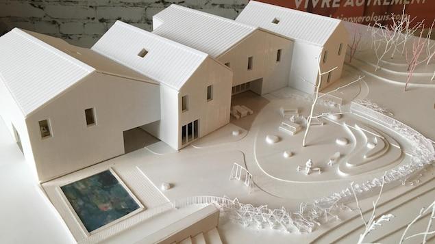 Maquette blanche d'un édifice composé de quatre bâtiments.