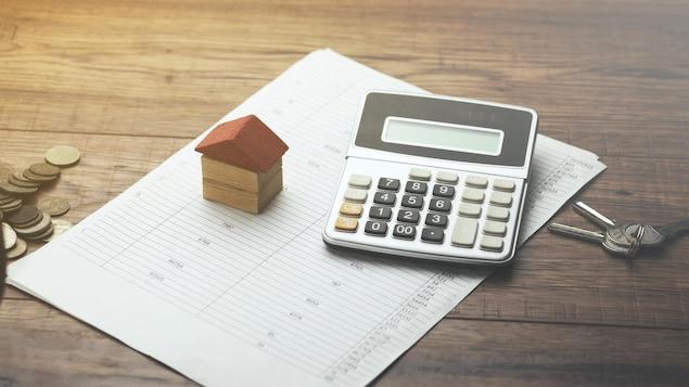 Une calculatrice et une maison miniature se tiennent sur une feuille de calcul.
