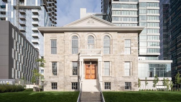 La maison restaurée, de l'extérieur, entourée de tours à condos au centre-ville de Montréal.