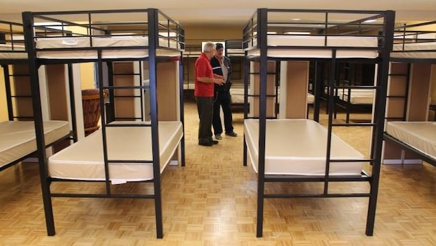 Deux personnes qui marchent entre des lits à étage dans un refuge.