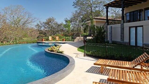 Vue d'une piscine bordée de transats en bois et d'une maison aux murs clairs.