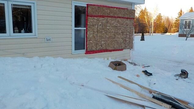 Une planche de contreplaqué recouvre les fenêtres fracassées de la maison des Porter.