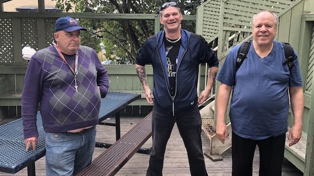 Trois hommes regardent l'objectif.