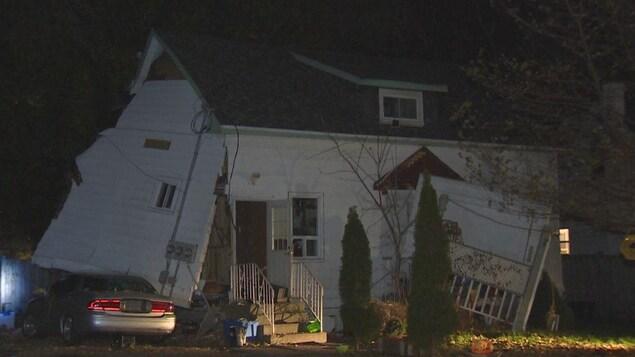 Photo d'une maison blanche dont l'un des murs est détaché de sa structure.